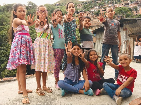 Children in the Ladera hillside neighborhood hold up their painted hands, which read: Fondo LEO