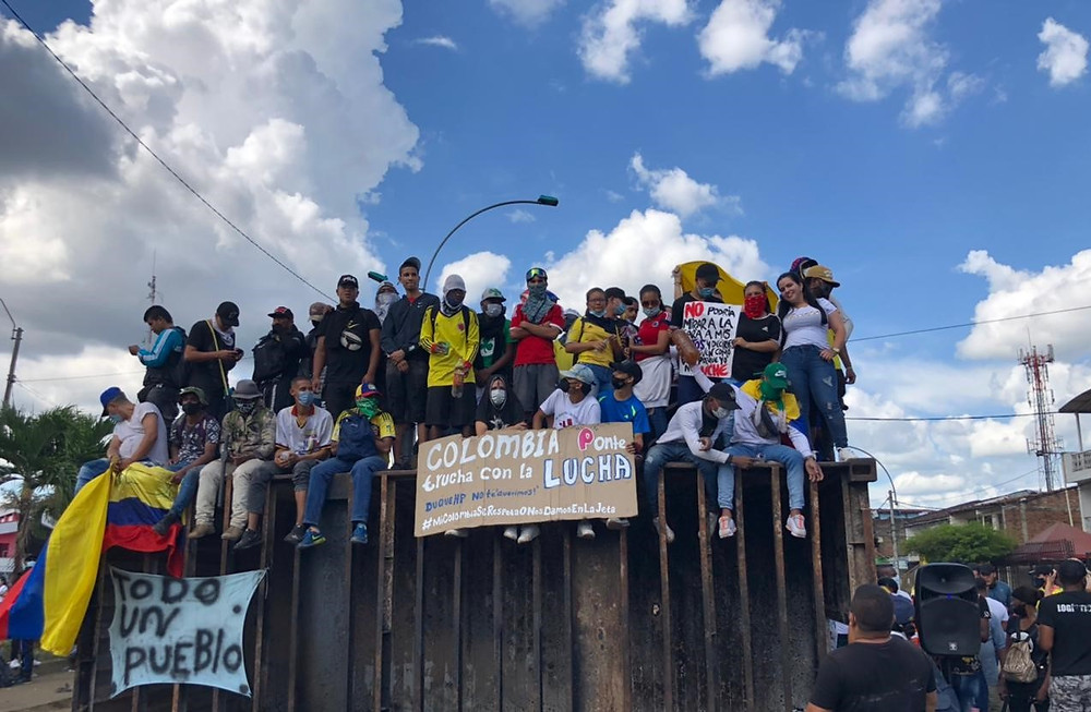 People gather to protest tax reform and government corruption in Cali, Colombia, carrying signs and flying the Colombian flag.