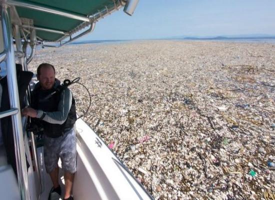 Homem em uma embarcação no meio de uma Ilha de plástico, a superfície do mar estáa coberta por resíduos sólidos.