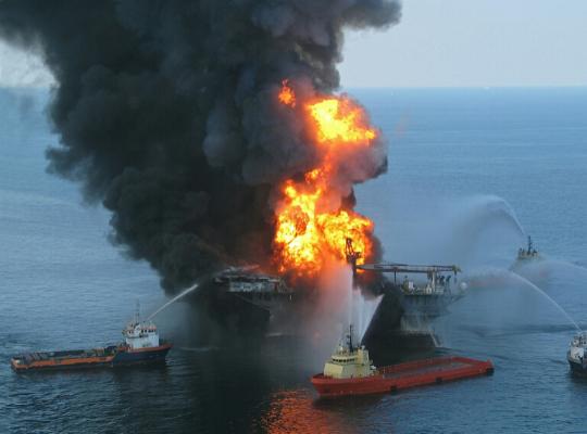 Imagem da plataforma pegando fogo. Uma fumaça cinza escuro está saindo enquanto quatro navios pipa estão jogando água para tentar controlar o fogo.