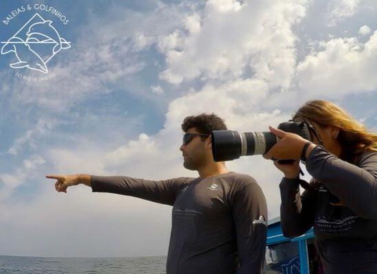 Imagem de um homem e uma mulher embarcados. O homem está apontando o dedo da mão direita para o mar e a mulher posicionada do seu lado esquerdo está segurando um câmera fotográfica apontada na mesma direção. O seu está aberto, com nuvens brancas.