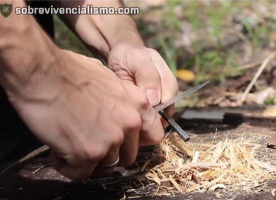 Mãos de uma pessoa à esquerda da foto fazendo fogo com uma faca e uma pederneira. No centro da imagem há um pequeno monte de fibras de taboca (semelhante a bambu). No fundo, é possível visualizar grama, pedras e árvores.