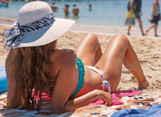 Imagem de uma mulher biquini e chapéu tomando sol na praia deitada sobre uma canga.