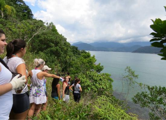 Pessoas andando em fila em uma trilha no Costão Rochoso, ao contato com a mata e o ar puro, contemplam a linda vista do mar.