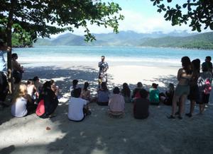 Foto de um grupo de pessoas na praia. Algumas estão sentadas, outras em pé, todas olhando para o professor em pé à frente deles. Estão sob a sombra de de duas árvores e, ao fundo, o mar e alguns morros.