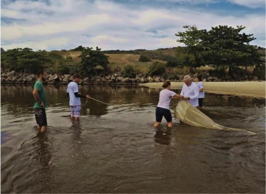 Na fotografia, vemos uma equipe de 5 pesquisadores realizando uma coleta de zooplâncton na maré vazante, utilizando uma rede de plâncton, que tem formato de uma peneira profunda em um canal. Os pesquisadores estão com água até os joelhos. Ao fundo observa-se a beira do rio com rochas acinzentadas, vegetação arbustiva esverdeada e, por fim, o céu azul com nuvens.