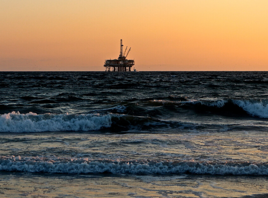 Imagem mostrando o oceano com algumas ondas no plano anterior da foto. Ao fundo aparece uma plataforma de petróleo. O céu está com a tonalidade laranja.