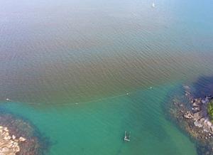 A imagem apresenta uma mancha com cor diferente da água do mar, com tom avermelhado, no canal de São Sebastião, São Paulo. O canto inferior da imagem mostra a região costeira do canal com agregados de rochas.