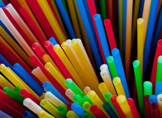 Foto de vários canudos plásticos coloridos vistos de cima.