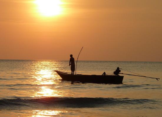 Foto de um pescador em pé na extremidade de uma canoa e com vara de pesca. . O barco aparenta estar próximo da praia devido a presença de ondas pequenas. O sol está se pondo e o céu está cor laranja