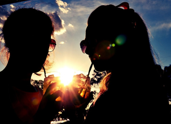 Silhueta de duas mulheres usando canudo para consumir uma bebida. Atrás delas, céu azul com poucas nuvens e a luz do sol refletindo nos copos que elas seguram.