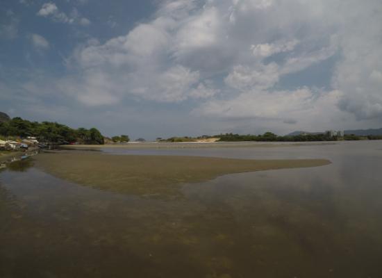 A fotografia mostra uma Laguna sendo vista por sua margem. As margens da lagoas são constituídas por vegetação esverdeada e pode-se observar interferência antrópica. O céu é azul com nuvens.