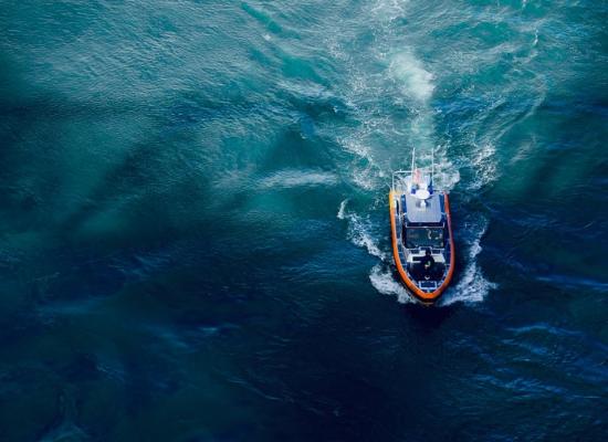 Imagem mostrando de cima o oceano e uma embarcação.