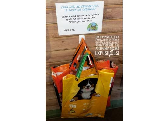 Imagem com fundo de madeira e sacolas feitas de sacos de ração expostas para venda e um cartaz explicativo sobre o produto.
