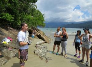 Foto de professor e alunos em curso de Biologia Marinha do projeto Bióicos antes de iniciar uma trilha em área de Mata Atlântica com mar à direita e montanhas ao fundo. Os alunos estão voltados para o professor, que passa instruções.