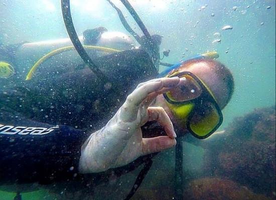 Foto da metade superior do mergulhador com cilindro olhando para a câmera e fazendo OK com a mão direita.