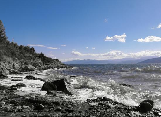 Costa marinha. À esquerda, praia rochosa com tons cinzas e e vegetação arbustiva. À direita, mar acinzentado com ondas quebrando sobre a praia. No fundo, céu azul com nuvens e sobras de ilhas ano fundo da paisagem.