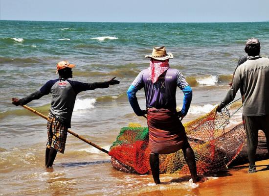 Foto de três pescadores organizam as redes para a pesca na beira do mar, o primeiro se encontra com um leme na mão, o segundo observa e o terceiro prepara as redes.