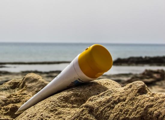 Protetor solar jogado na areia. Ao fundo temos uma imagem desfocada do mar e algumas rochas.
