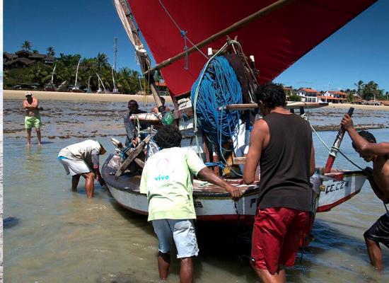 Foto de pescadores que retiram uma jangada do mar em direção à praia, um turista observa ao fundo a atividade, a faixa de praia é composta por muitas árvore, casas e jangadas.