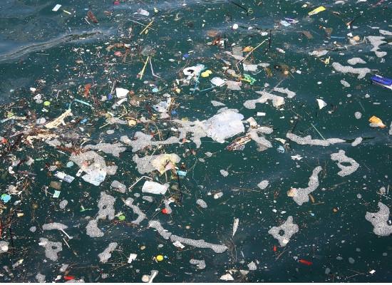 Foto da água do mar vista de cima, com muitos objetos flutuando em meio a blocos de espuma.