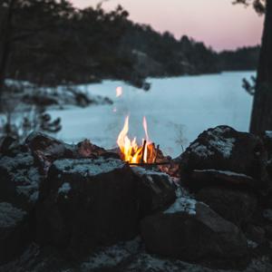Fotografia de uma fogueira com fogo vermelho-alaranjado aceso atrás de pedras grandes. No fundo, é possível ver um curso d'água, mata ciliar e o céu azul-arroxeado. Há a silhueta de duas árvores, uma de cada lado da imagem.