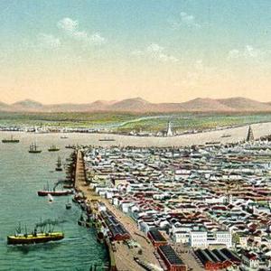 A foto mostra uma pintura do século XX do porto de Santos com algumas embarcações atracadas outras se aproximando dos atracadouros. Também é possível observar muitas residências ao redor do porto.
