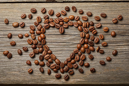 Heart shape made from coffee beans on wo