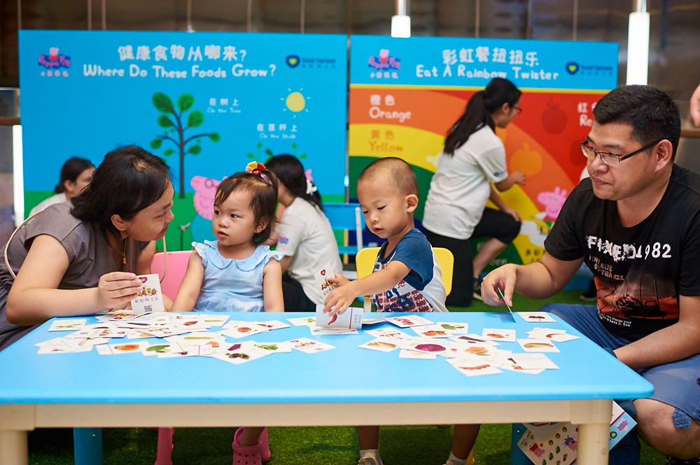 Parents playing with their children at the pop-up using Food Heroes Flashcards