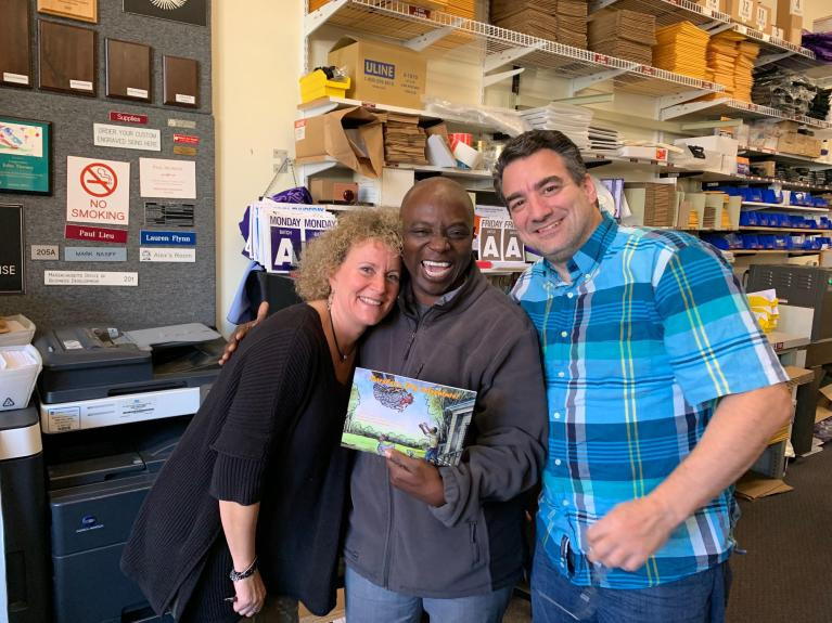 """Gordon Halm, executive director and founder of the African Community Center of Lowell, (center) shows of a copy of children's book ""Parsley's Big Adventure."" Also pictured are Michelle and Peter Bergeron, of OwlStamp Visual Solutions, which put the book together for print. COURTESY PHOTO"""