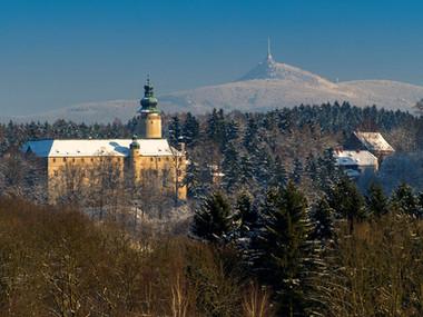 Zámek Lemberk v pozadí s Ještědem v zimě