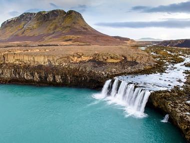 Vodopád Þjófafoss na řece Þjórsá v pozadí s vrchem Búrfell