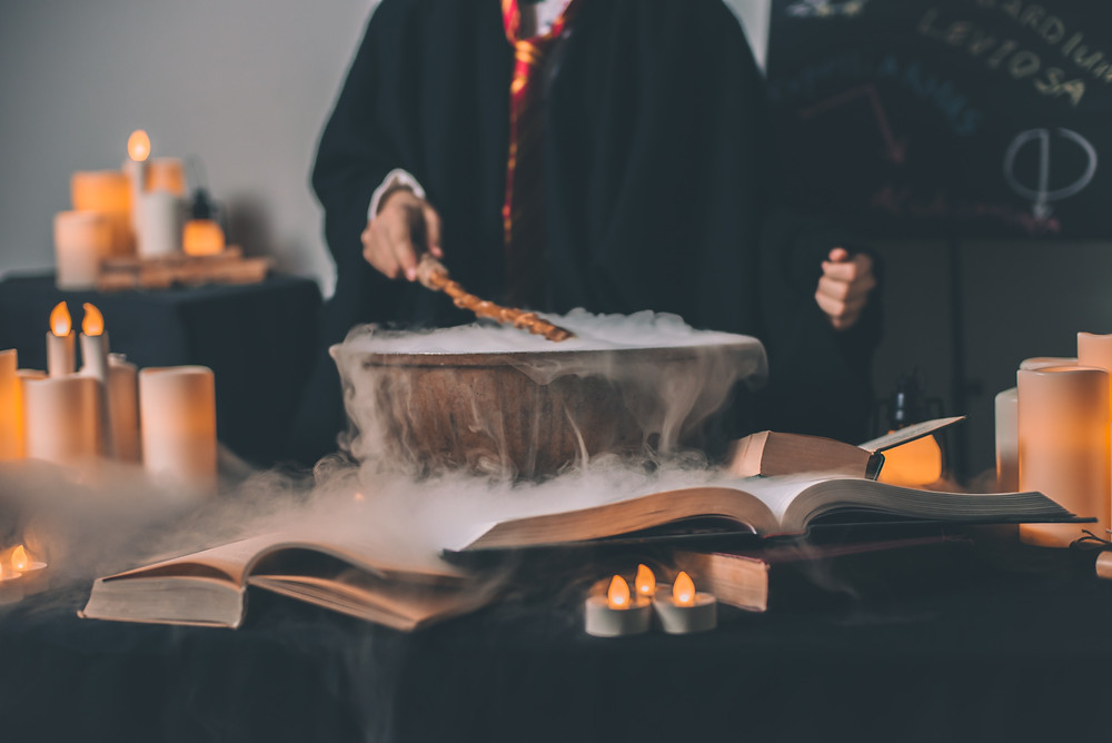 A person is holding a wand over a smoking bowl near candles.
