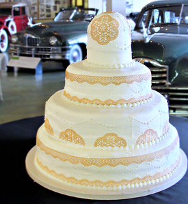 5 tiered cake featuring intricate piping and edible lace work.