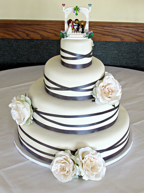 Crisp marshmallow fondant draped cake featuring ribbon accents and a playful topper!