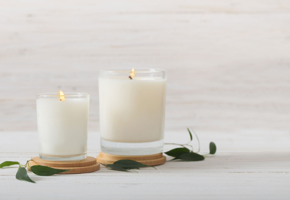 2 white candles in glass jars burning