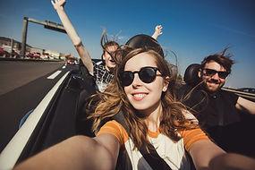 Happy group of friends taking selfie whe