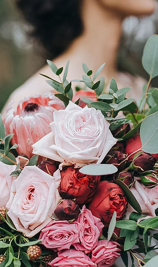 Bouquet of wedding flowers, mostly roses and some eucalyptus and berries. Pinks and reds.