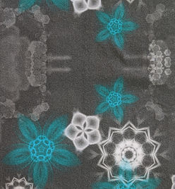 dark grey fabric design with white and turquoise flowers and geomteric shapes