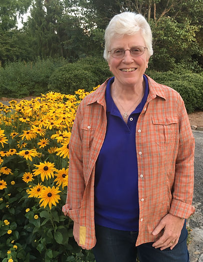 Annette Marquis standing by a bunch of black-eyed Susans.JPG