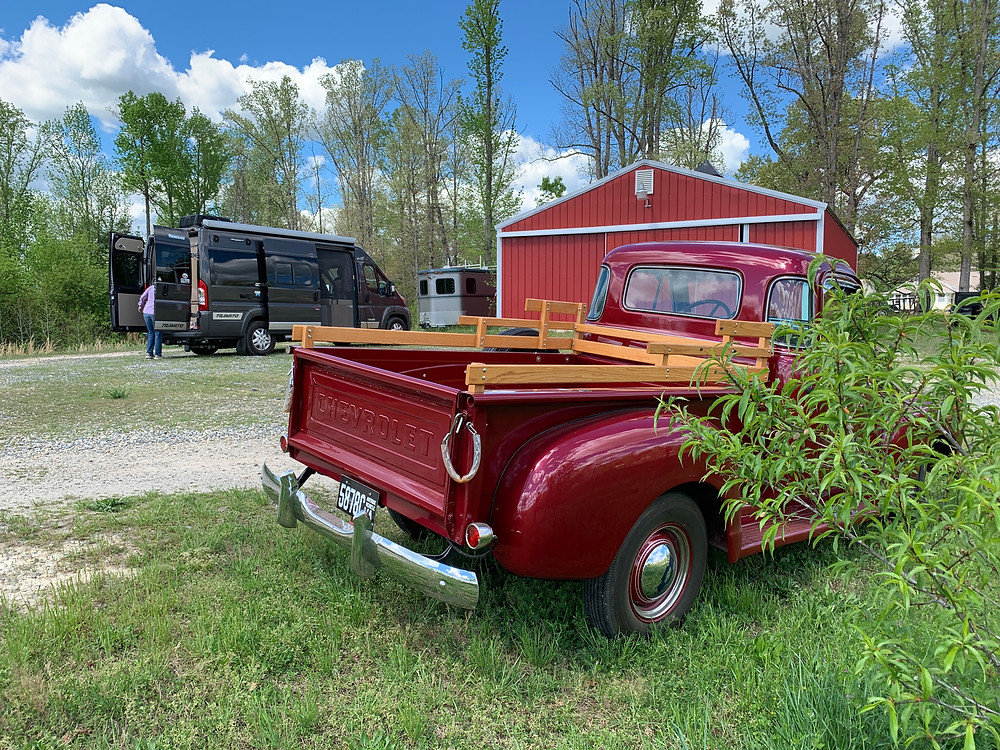 A new granite colored Winnebago Travato camper van and an antique Chevy truck parked near a red pole barn