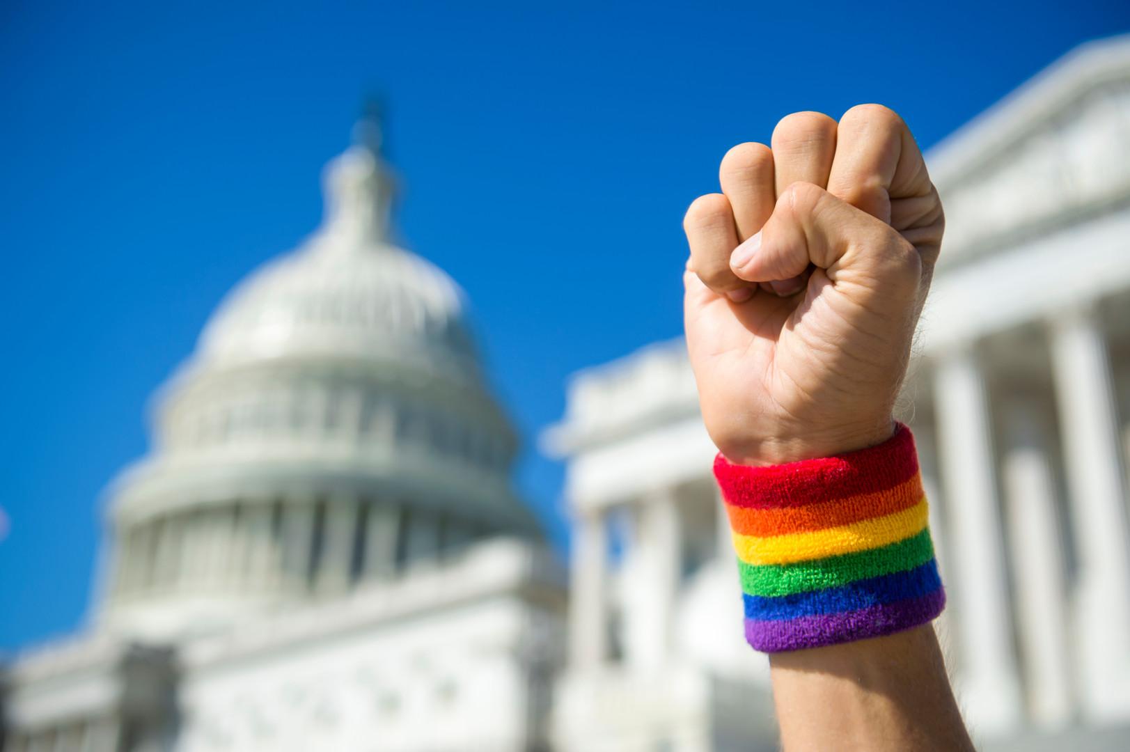 Hand wearing gay pride rainbow wristband
