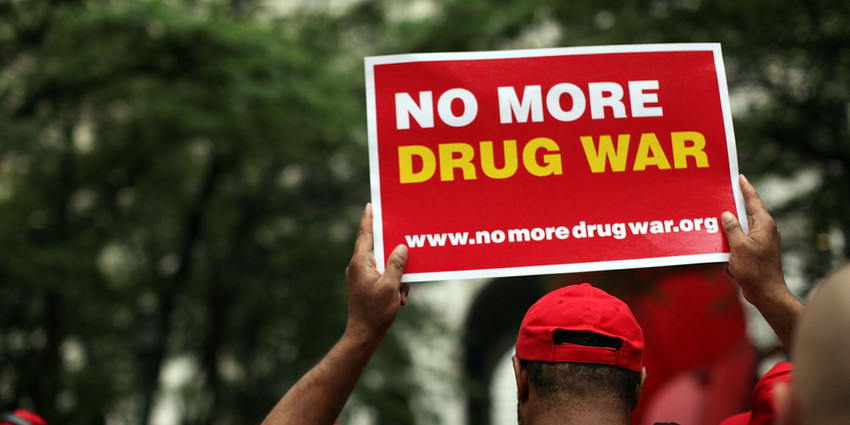 A protester holds a sign supporting an end to the War on Drugs
