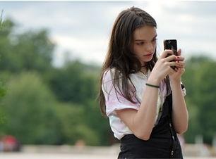 Jeune fille derrière smartphone.jpg