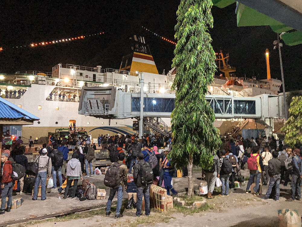 Picture of the pelni ferry in the harbour and people waiting to board to ferry