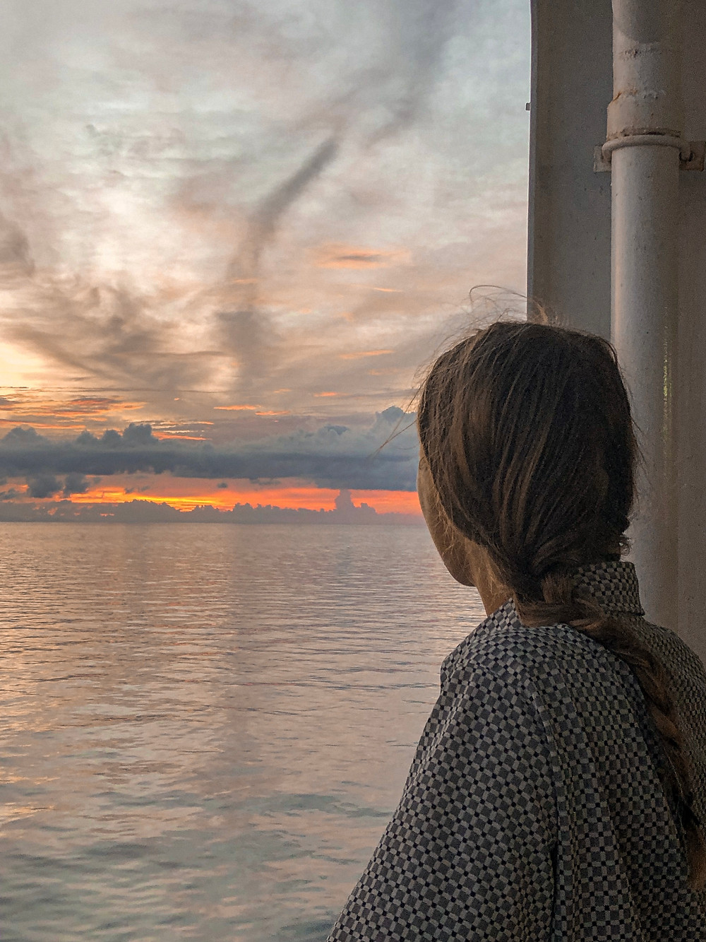 Woman standing on ferry and looking at the sunset
