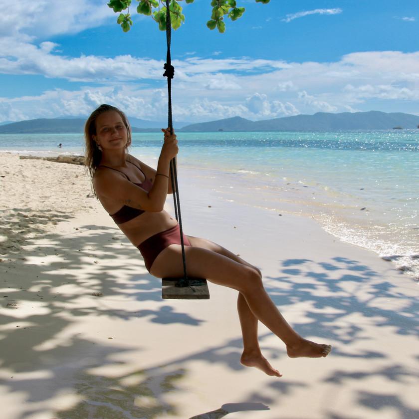 Woman on swing on beach in Raja Ampat