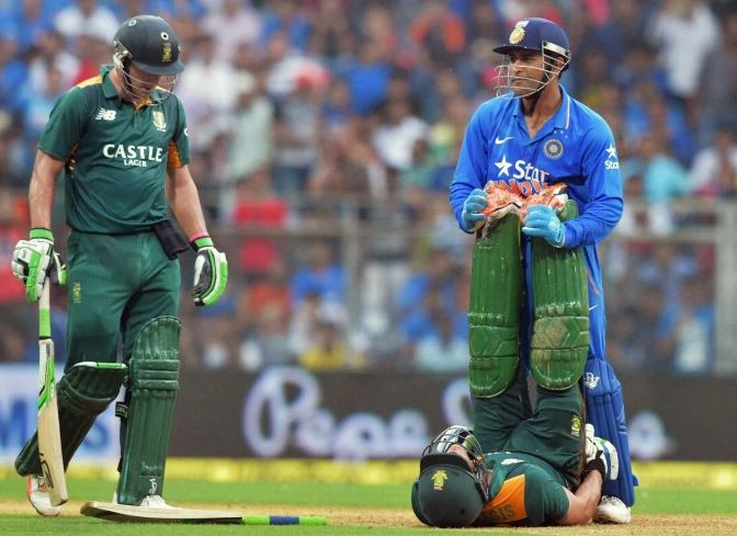 MS Dhoni helping a player during a cricket match