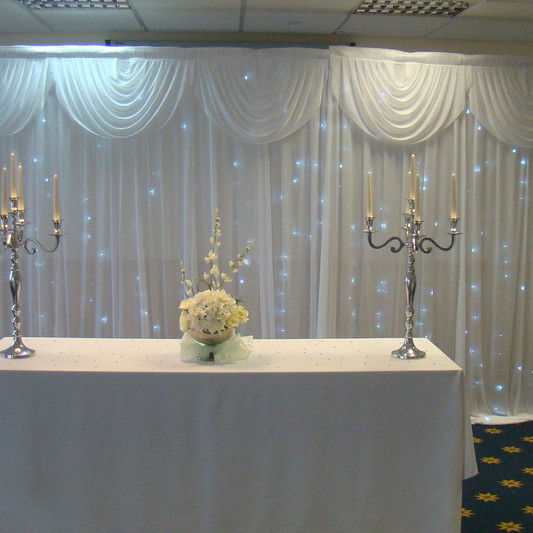 Ceremony room with candelabra, flowers and fairylight backdrop curtain