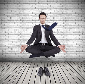 young businessman levitating in yoga pos